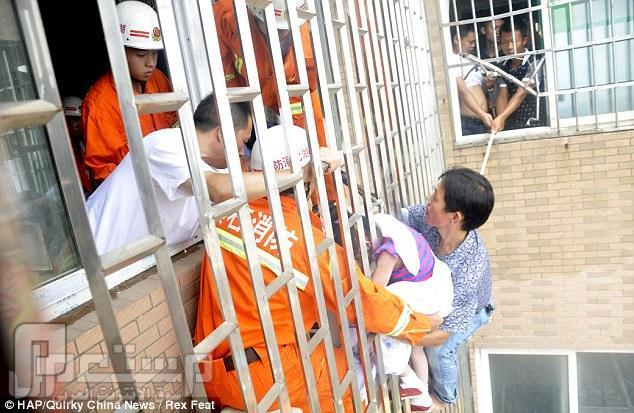 بالفيديو والصور.. إنقاذ طفلة صينية علق رأسها بين قضبان الطابق الـ 24