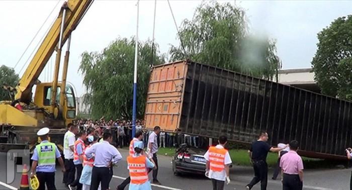 بالصور: صينية تنجو من الموت رغم سقوط حاوية نقل ضخمة على سيارتها
